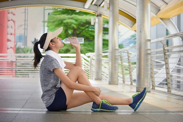 Água potável nova bonita da mulher de ásia após o treinamento.