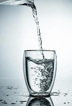 Água pura e fresca e fria é derramada em um copo. água purificada em um copo em uma parede cinza. movimento congelar respingo de água cristalina na parede cinza.