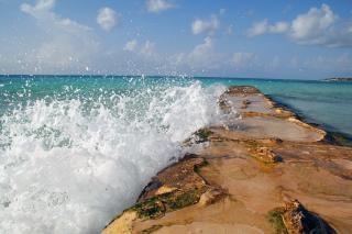 Água que quebra sobre uma barreira à beira-mar