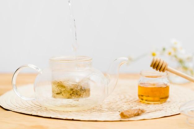 Água quente derramando no bule de chá