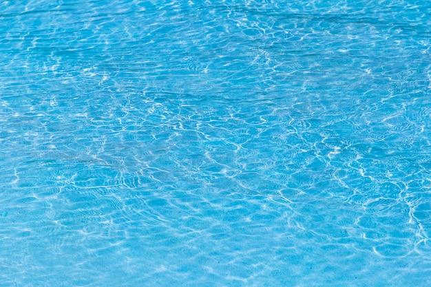 Água rasgada azul na piscina com reflexões ensolaradas.