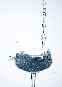 Água realista derramando em vidro
