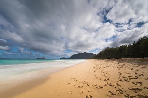 Água suave lavando na praia de waimanalo com a ilha do coelho