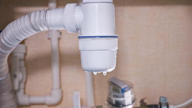 Água suja pinga de um coletor de encanamento de plástico branco danificado sob a pia na cozinha contemporânea sob luz forte, visão extrema de perto