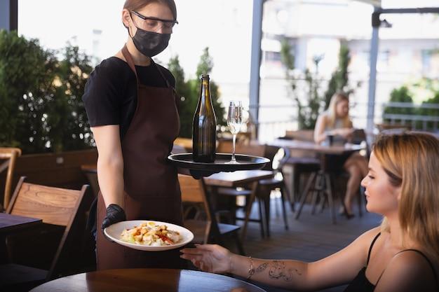 Água trabalhando com máscara facial em restaurante, surto de coronavírus