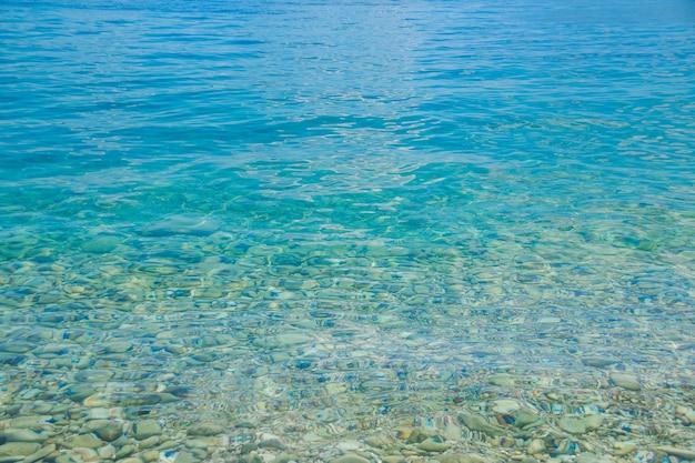 Água transparente com fundo rochoso.