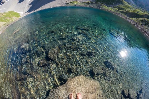 Água transparente no lago alpino, pés humanos, olho de peixe