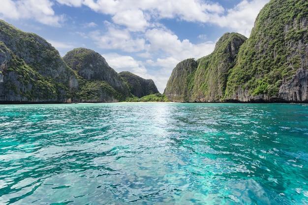 Água turquesa com montanhas com vegetação e nuvens em uma paisagem de céu azul