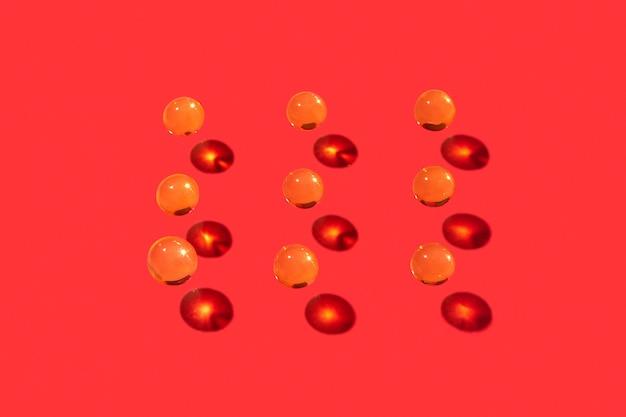 Água voando pequenas bolas de líquido de gel de cristal com sombras duras e reflexos em uma parede vermelha, lugar para texto.