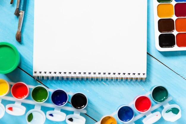 Aguarelas e guache para a criatividade infantil sobre uma mesa azul. copie o espaço.