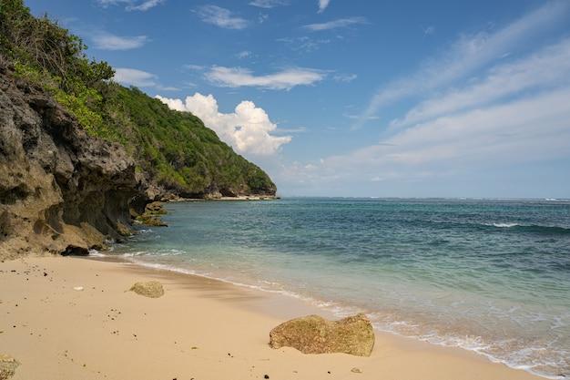 Águas azuis calmas em uma praia rochosa selvagem com areia dourada