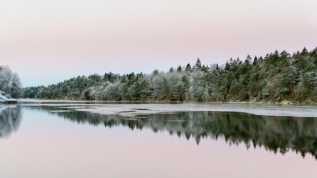 Águas calmas e reflexos das árvores e do céu.