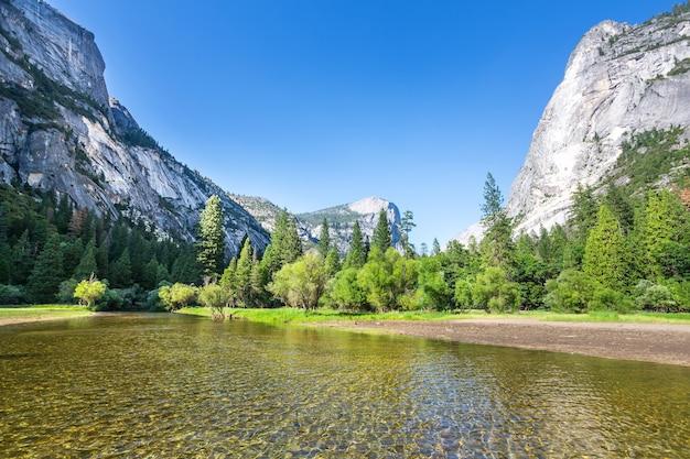 Águas claras e floresta de pinheiros perene cercada por montanhas de granito