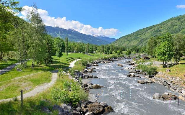 Águas correntes de um rio cruzando um parque de lazer em um vale de tarentaise nos alpes franceses
