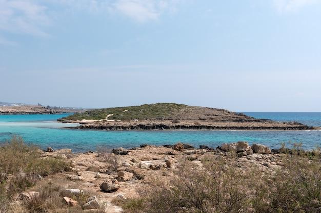 Águas cristalinas e rochas de arenito do mar mediterrâneo, chipre. baía do mar tropical paisagem, litoral de praia