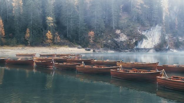 Águas esmeraldas do lago di braies e barcos de madeira com floresta nublada no fundo, dolomitas, itália