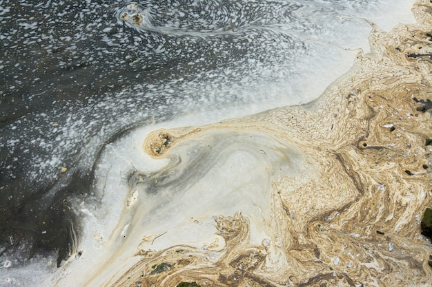 Águas extremamente poluídas, espuma branca e mancha de óleo no mar
