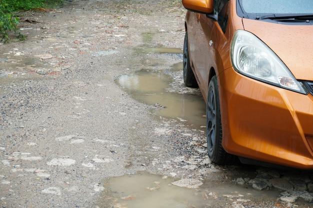Águas pluviais presas em uma estrada esburacada