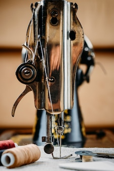 Agulha de aço com looper e um pé calcador de velho vintage mão máquina de costura close-up