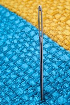 Agulha de costura em um fundo de tecido amarelo. fechar-se.