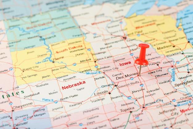 Agulha de escritório vermelha no mapa dos eua, iowa e a capital des moines. feche o mapa de iowa com aderência vermelha