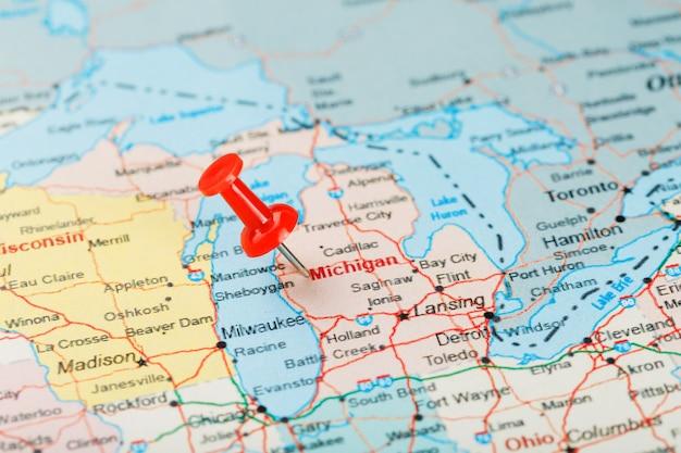 Agulha de escritório vermelha no mapa dos eua, michigan e a capital lansing. feche o mapa de michigan com aderência vermelha