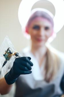 Agulha de espera de mestre de beleza de mulher para maquiagem permanente tattoo-gun mãos em luvas pretas