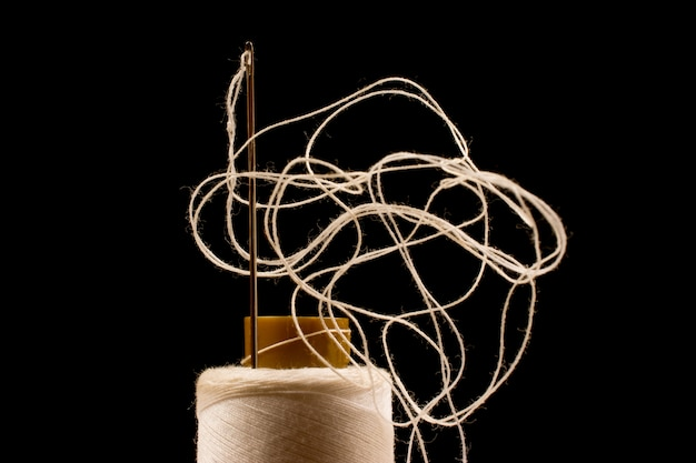 Agulha e algodão branco, fios emaranhados em rolo para costura. linha usada na indústria de tecidos e têxteis.