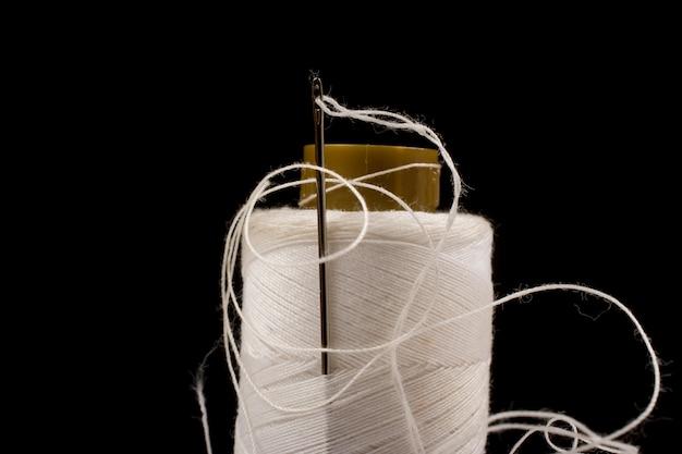 Agulha e algodão branco, fios emaranhados em rolo para costura.