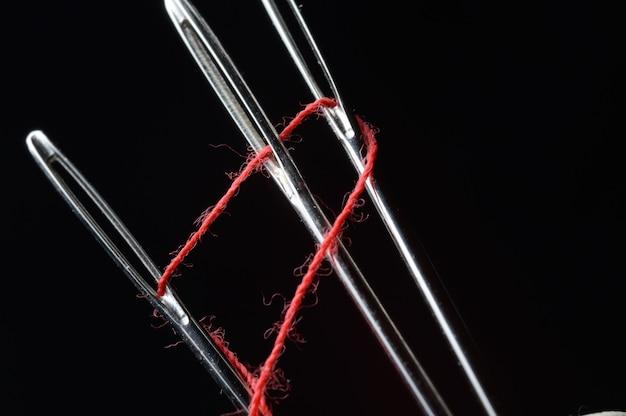 Agulha e linha vermelha