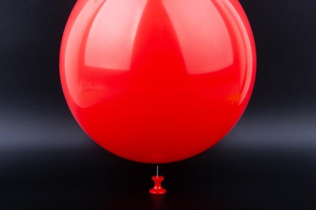 Agulha prestes a estourar um balão vermelho