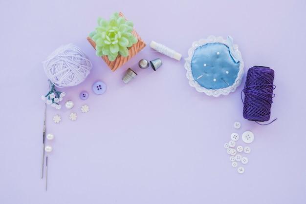 Agulhas com almofada de alfinetes; dedal; bola de lã; miçangas; carretel de botão e fio no pano de fundo roxo