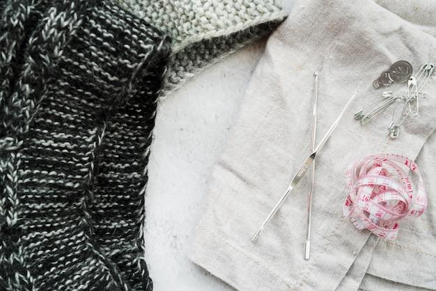 Agulhas de crochê; malha de malha; fita métrica; alfinetes de segurança em pano de fundo texturizado branco