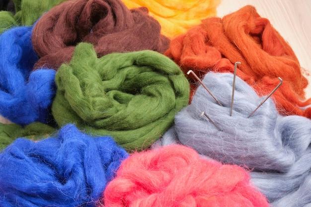 Agulhas de feltro e alguns novelos de lã de ovelha tingida natural em close-up da mesa