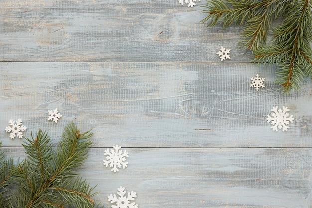 Agulhas de pinheiro em fundo de madeira com flocos de neve