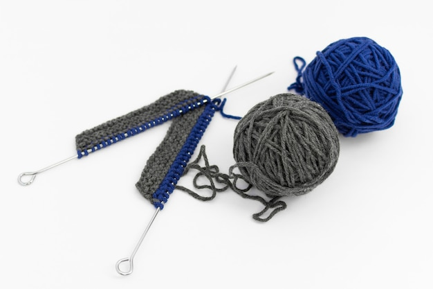 Agulhas de tricô com tricô e bolas de lã em fundo branco