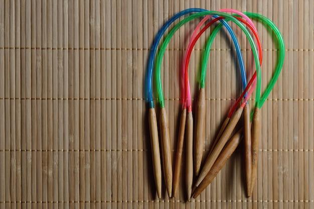 Agulhas de tricô de bambu circular em uma superfície de madeira.
