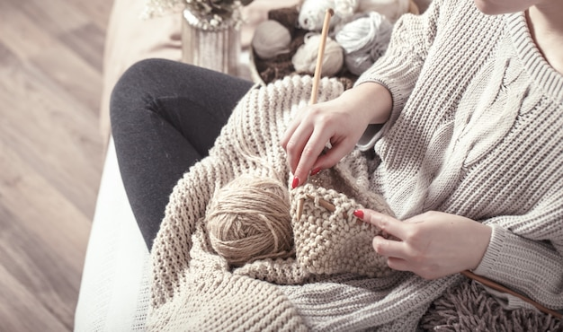 Agulhas de tricô de madeira vintage e fios em mãos femininas
