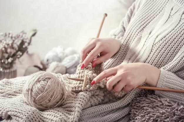 Agulhas de tricô de madeira vintage e fios nas mãos da mulher