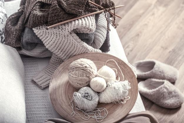 Agulhas de tricô de madeira vintage e linhas em um sofá aconchegante com almofadas e chinelos nas proximidades