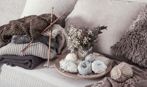 Agulhas de tricô de madeira vintage e linhas em um sofá aconchegante com almofadas e um vaso de flores