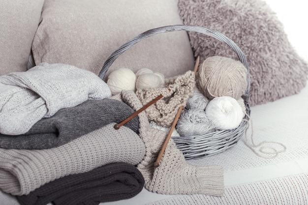 Agulhas de tricô de madeira vintage e linhas em uma grande cesta em um sofá aconchegante com blusas. ainda vida foto