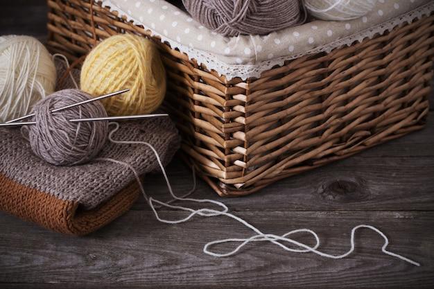 Agulhas de tricô e tricô em uma superfície de madeira