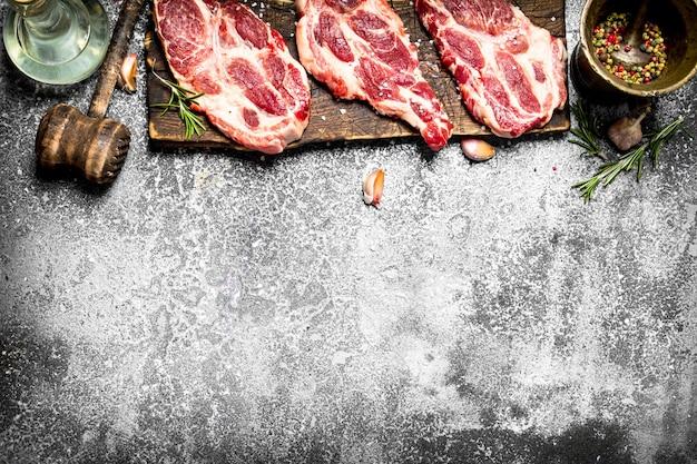 Ah, fundo de carne. carne de porco crua com especiarias e ervas. sobre uma mesa rústica.