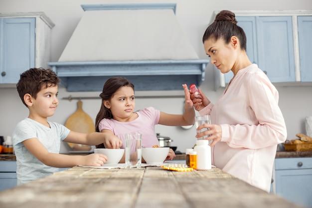 Ah não. garotinha de cabelos escuros muito irritada tomando café da manhã com o irmão e se recusando a tomar vitaminas que sua mãe estava dando a ela