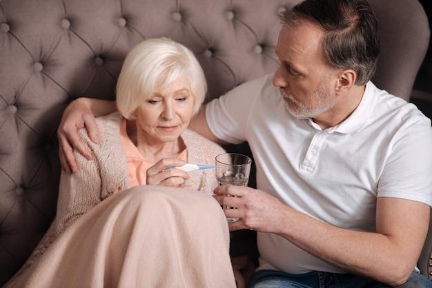 Ah não. mulher idosa triste sentada coberta com um cobertor quente perto de seu marido amoroso, segurando o copo de água e verificando o termômetro.