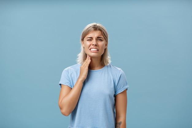 Ai minha garganta. menina loira adulta bonita e infeliz, com corte de cabelo curto, cerrando os dentes por causa da sensação de dor tocando no pescoço, tendo angina ou posar de inflamação