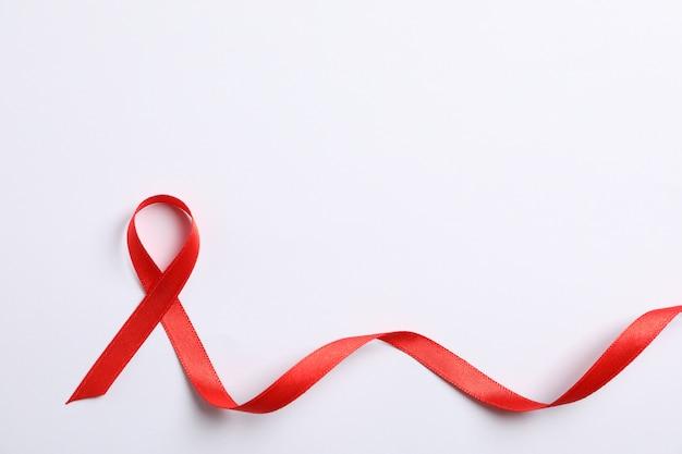 Aids fita vermelha de conscientização na parede branca, espaço para texto