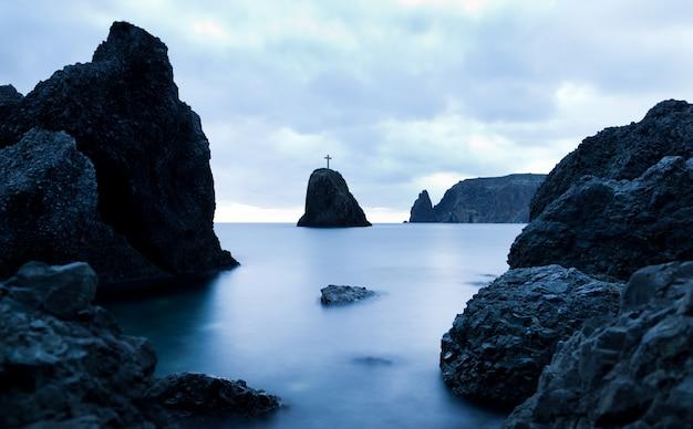 Ainda águas do mar, pedras duras e cruzam no pico da rocha na noite num dia de verão com céu sombrio no fundo