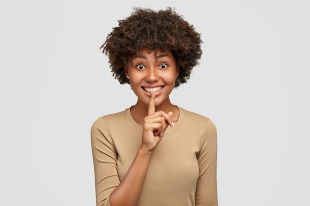 Ainda bem que a adorável mulher afro-americana pede para ficar em silêncio, segura o dedo indicador nos lábios, tem uma expressão alegre, vestida casualmente, posa contra uma parede branca. conceito de pessoas, sigilo e etnia